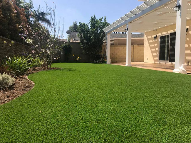 Artificial grass backyard installation with natural stone travertine pavers patio remodel in Anaheim, CA